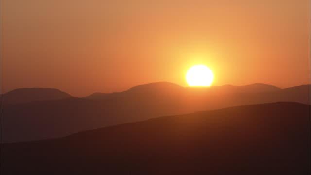 a blazing sun rises past desert mountains. - heat stock videos & royalty-free footage