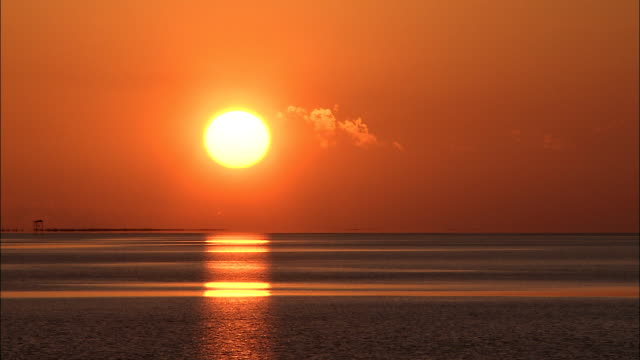 a blazing sun sets over a calm ocean. - 宇宙・天文点の映像素材/bロール