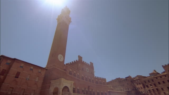 a blazing sun shines down on the spectacular torre del mangia and plazzo pubblico in siena, tuscany, italy. - palazzo pubblico stock videos and b-roll footage