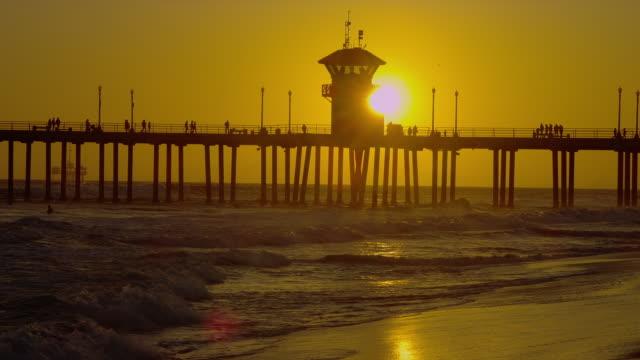 stockvideo's en b-roll-footage met a blazing sun silhouettes huntington beach pier. - houten paal