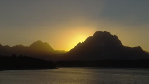 a blazing sun silhouettes the grand teton mountains as it sets beyond jackson lake in grand teton national park. - teton range stock videos & royalty-free footage