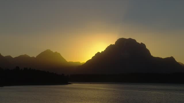 vídeos y material grabado en eventos de stock de a blazing sun silhouettes the grand teton mountains as it sets beyond jackson lake in grand teton national park. - cordillera tetón
