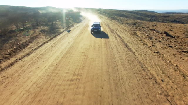blazing through the namibian desert - strada in terra battuta video stock e b–roll