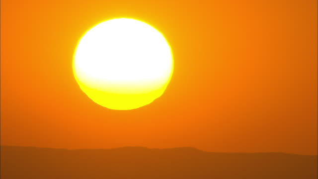 a blazing yellow sun sets in an orange sky. - sunlight stock videos & royalty-free footage