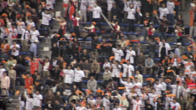 ws pan bleachers at baseball stadium full of fans cheering, waving orange towels, and moving in synchronized motion during game / tokyo, tokyo prefecture, japan - baseball sport stock videos & royalty-free footage