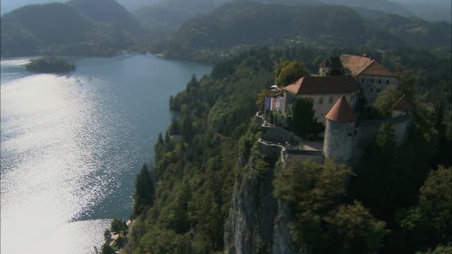 vídeos de stock e filmes b-roll de aerial bled castle and lake bled / slovenia - lago bled