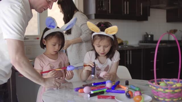 gemischte familie schmückt ostereier zusammen - happy easter stock-videos und b-roll-filmmaterial