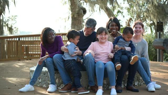 blended family, five children all sit together, laughing - tvåföräldersfamilj bildbanksvideor och videomaterial från bakom kulisserna