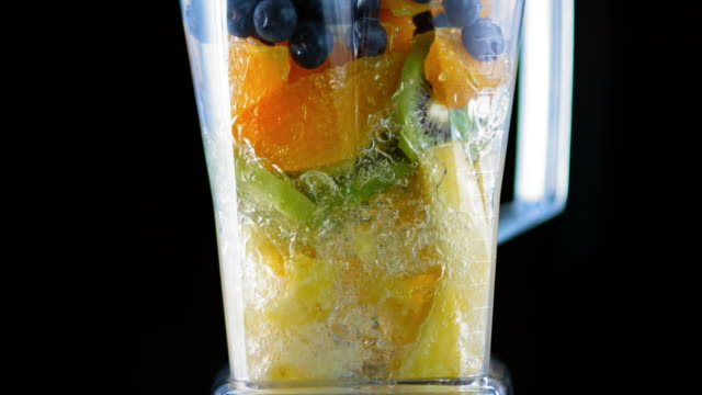 slo mo blender blending fruit on black background - smoothie stock videos & royalty-free footage