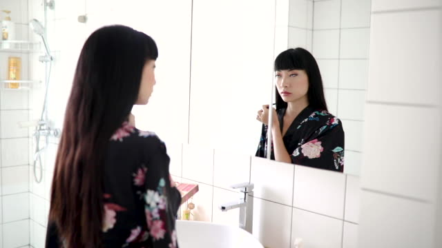 blending her makeup for a natural look - bathroom sink stock videos & royalty-free footage