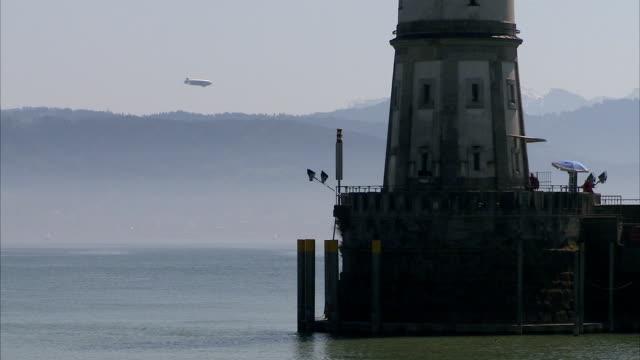 a blimp flies near a lighthouse in lindau, germany. - bavarian alps stock videos & royalty-free footage
