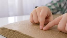 blind kid hands reading braille book with symbols font for Visually impaired close up sitting at table