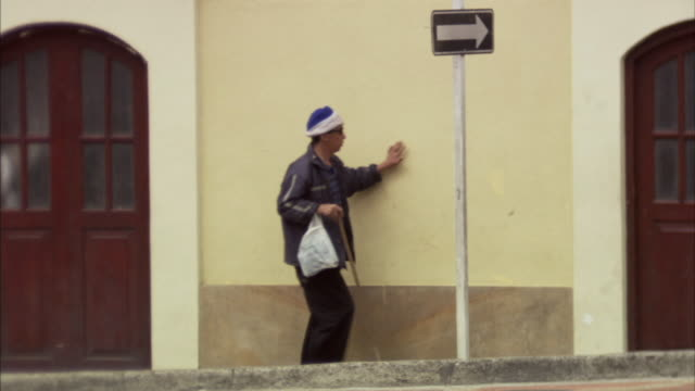 ws blind man walking and feeling his way along wall near arrow sign / bogota, colombia - blindness stock videos & royalty-free footage