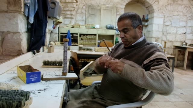 blind palestinian worker makes a broom at the workshop owned and managed by the arab blind association, which was founded by blind palestinians in... - eddie gerald stock videos & royalty-free footage