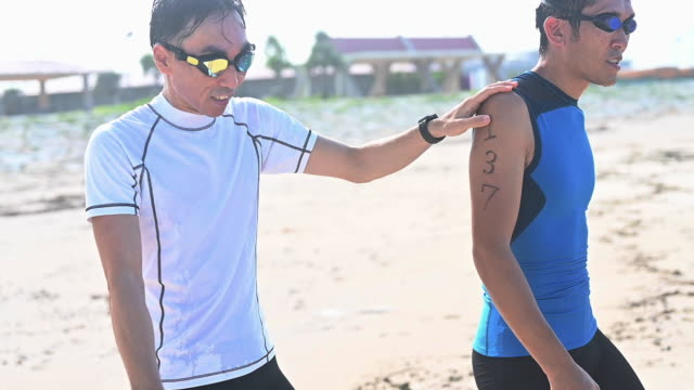 blind triathlete training on the beach - guidance stock videos & royalty-free footage
