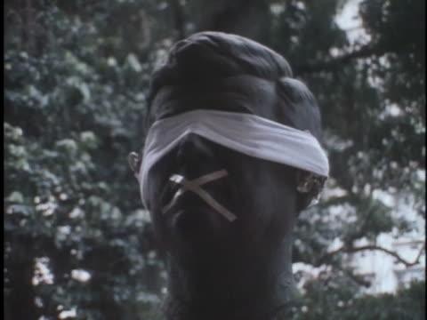 blindfolded eyes and taped mouth on a bust provide symbols against brazilian government oppression. - dominering bildbanksvideor och videomaterial från bakom kulisserna