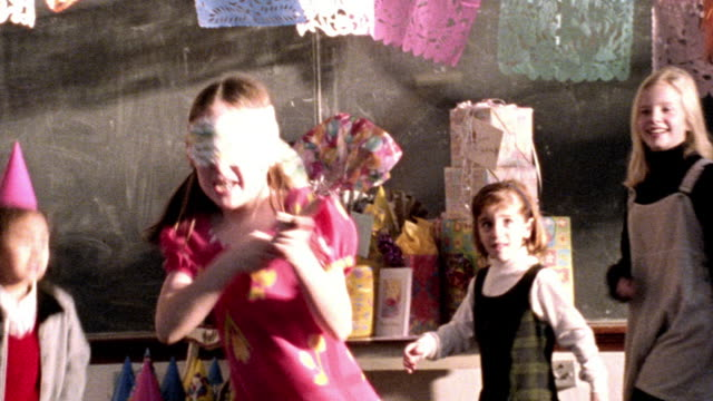 high contrast ms blindfolded girl swings stick at pinata / group of excited girls run around her - papier stock videos & royalty-free footage