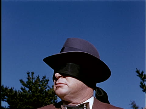 1965 CU Blindfolded man in hat with blue sky background