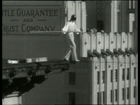 1936 B/W blindfolded man walking on tightrope between buildings / Los Angeles / NO AUDIO