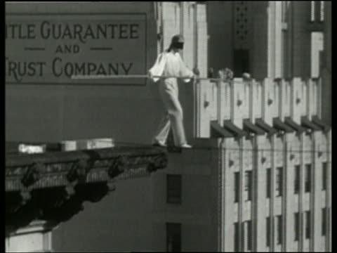 vídeos y material grabado en eventos de stock de 1936 b/w blindfolded man walking on tightrope between buildings / los angeles / no audio - alambre