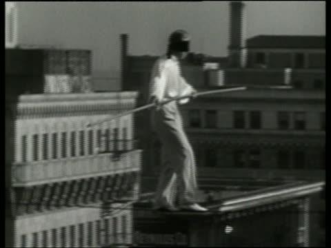 1936 b/w blindfolded man walking on tightrope between buildings / los angeles / no audio - tightrope walking stock videos & royalty-free footage