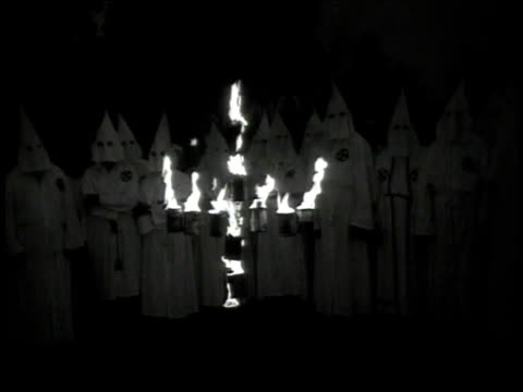 vídeos de stock, filmes e b-roll de montage blindfolded men being led by a kkk member in white robes to a rally where crosses are burning / georgia united states - ku klux klan