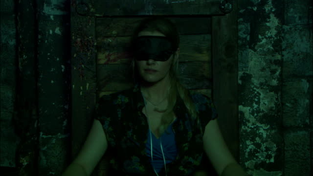 a blindfolded young woman struggles in her bonds. - dungeon stock videos & royalty-free footage