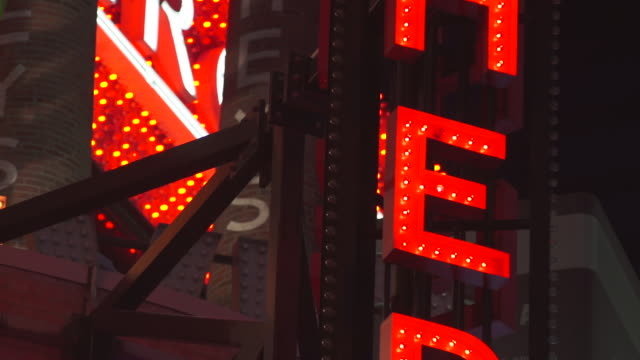 a blinking broadway style sign outside the hershey store in time square - ブロードウェイ点の映像素材/bロール