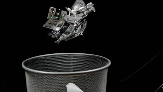 SLO MO Blister packs falling into wastepaper basket