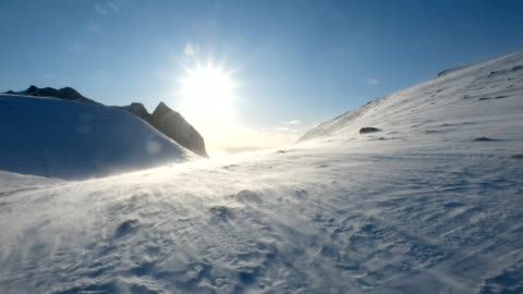 blizzard blowing on snowy mountain with sunshine - mountain stock videos & royalty-free footage