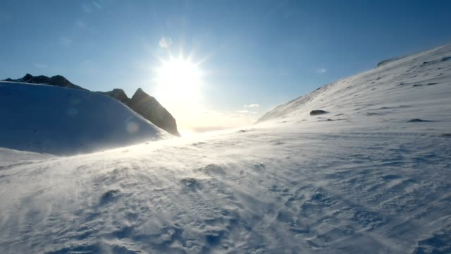 stockvideo's en b-roll-footage met blizzard blazen op besneeuwde berg met de zon - winter