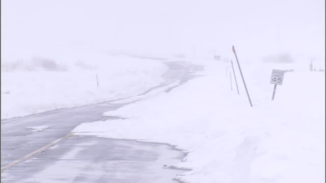 a blizzard creates white-out conditions on a desolate roadway. - 状態点の映像素材/bロール