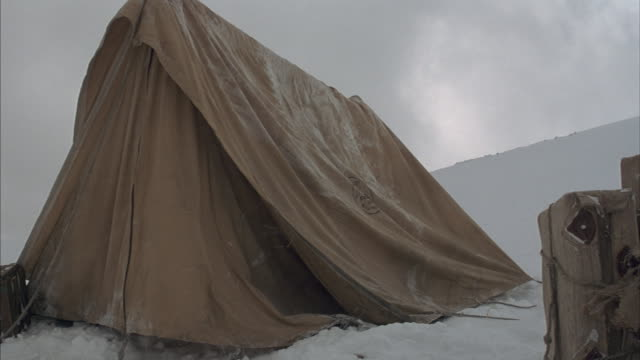 stockvideo's en b-roll-footage met a blizzard on a tibetan mountainside knocks down a tent and blows supplies away. - canvas