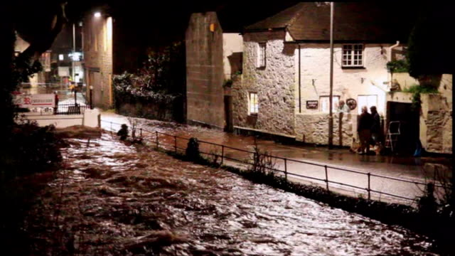 blizzards and torrential rain sweep the country; england: cornwall: newlyn: at night floodwater flowing swiftly along after torrential rain swollen... - ペンザンス点の映像素材/bロール