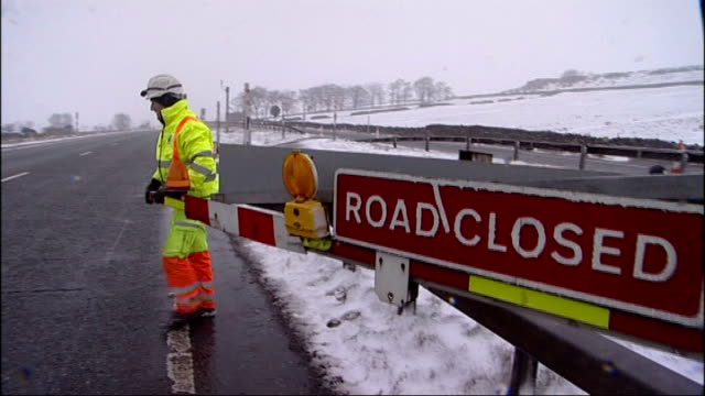 """blizzards and torrential rain sweep the country; england: county durham: snow being dug from under wheels of lorry """"road closed"""" sign on barrier... - road closed englisches verkehrsschild stock-videos und b-roll-filmmaterial"""