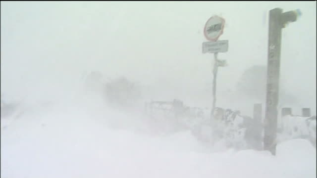 blizzards and torrential rain sweep the country england ext blizzard blowing across snow covered countryside and road car along slush covered road... - slush stock videos and b-roll footage