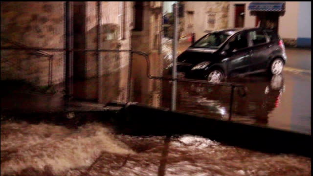 blizzards and torrential rain sweep the country; england: south west: floodwater on street floodwater flowing down street after heavy rain cornwall:... - ペンザンス点の映像素材/bロール