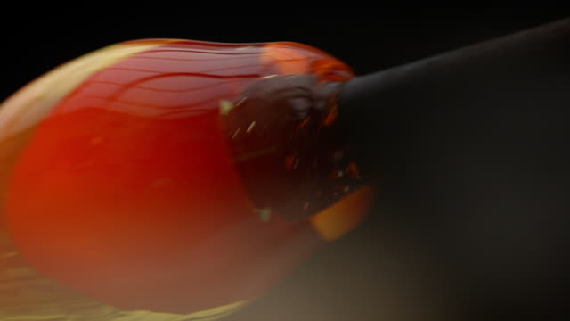 vidéos et rushes de a blob of molten glass is rolled on the end of a pipe in a glassblowing workshop. - art et artisanat