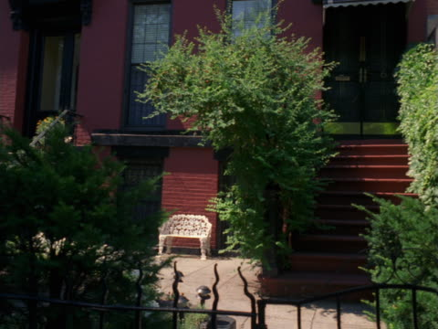 a block in brooklyn of brick row houses with many trees and shrubs. - artbeats stock videos & royalty-free footage