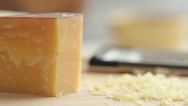cu block of gourmet cheese is set on to kitchen chopping block beside cheese shavings and man take up and tahe down chees on kitchen / los angeles, california united states - チーズ点の映像素材/bロール