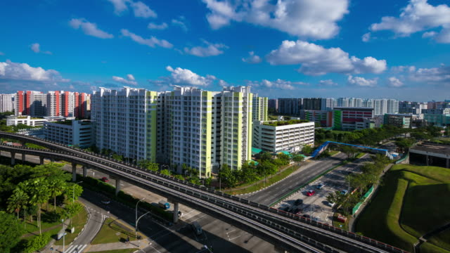 hdb block, overland mrt block and road traffic in buangkok, singapore (timelapse) - geplante wohnsiedlung stock-videos und b-roll-filmmaterial