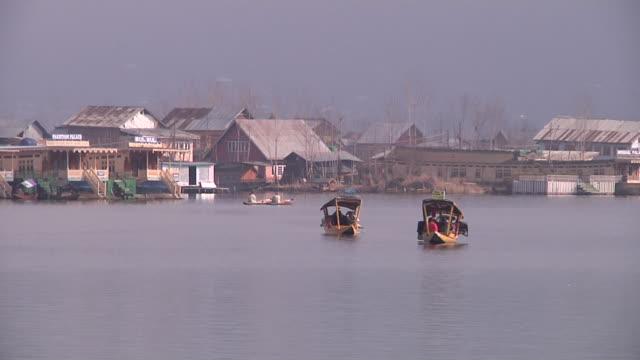 block shot shikara passing dal lake srinagar jammu kashmir - jammu e kashmir video stock e b–roll