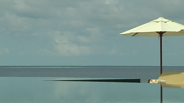 block shot swimming pool male maldives - infinity pool stock videos & royalty-free footage