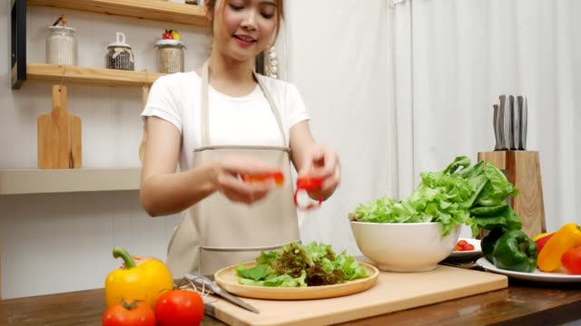 blogger asian woman making salad healthy food in kitchen at home. female prepare food concept. - making salad stock videos & royalty-free footage