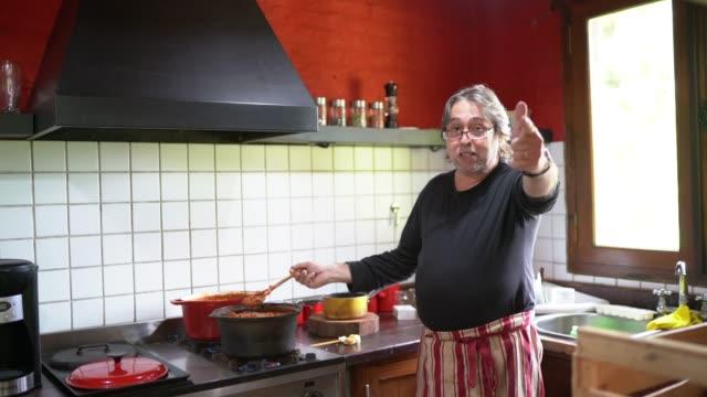 uomo blogger che cucina e parla con i follower a casa in cucina - one senior man only video stock e b–roll