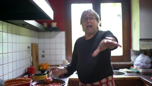 vidéos et rushes de homme de blogueur cuisinant et parlant aux disciples à la maison de cuisine - caméscope