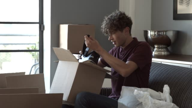 blogger unpacking box and wearing vr goggles on sofa - 段ボール箱点の映像素材/bロール