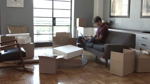 blogger using laptop while sitting on sofa surrounded by boxes - relocation stock videos & royalty-free footage