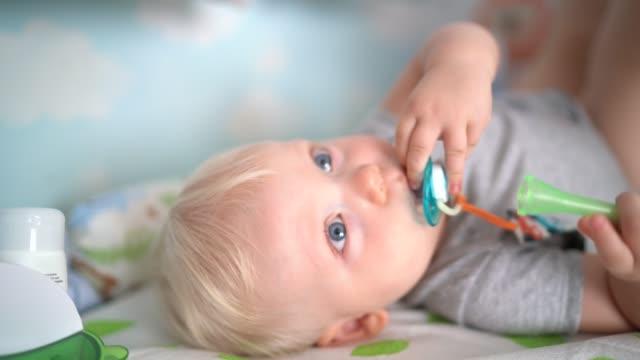 vídeos de stock, filmes e b-roll de os azul-olhos louros do bebé que encontram-se para baixo - olhos azuis