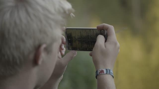 Blonder Junge Telefon Fotografieren der Waldteich